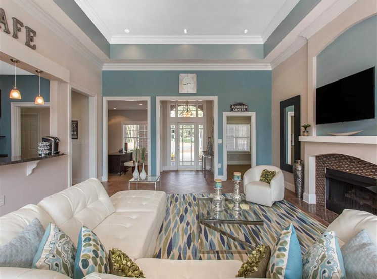 Clubhouse Seating Area with White Couch Glass Coffee Table and End Tables on Area Rug in Front of Fireplace with Mounted TV