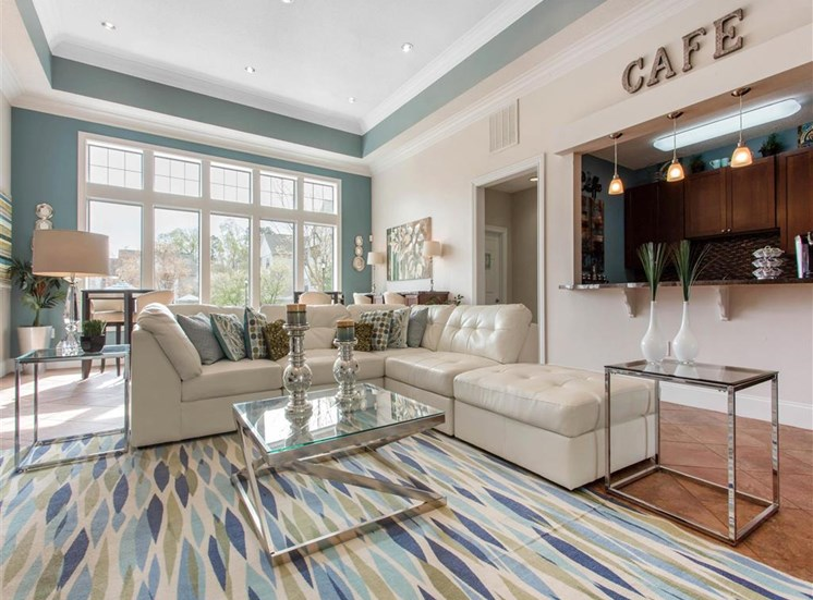 Clubhouse Seating Area with White Couch Glass Coffee Table and End Tables on Area Rug in Front of Clubhouse Kitchen
