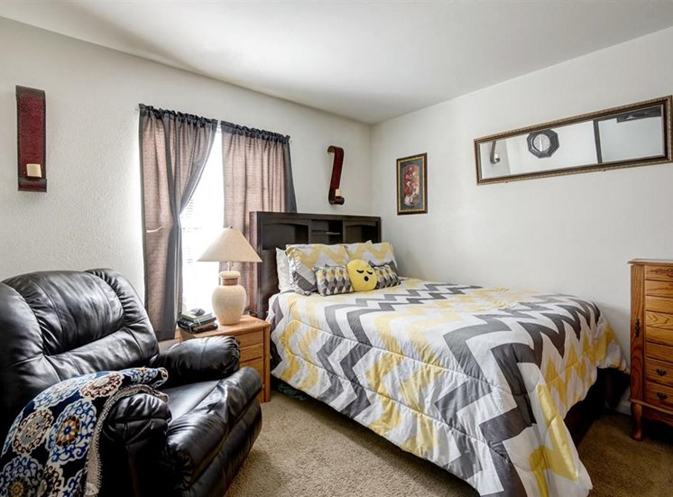 Model Bedroom with Large Window Recliner Bed Night Stand and Chest of Drawers