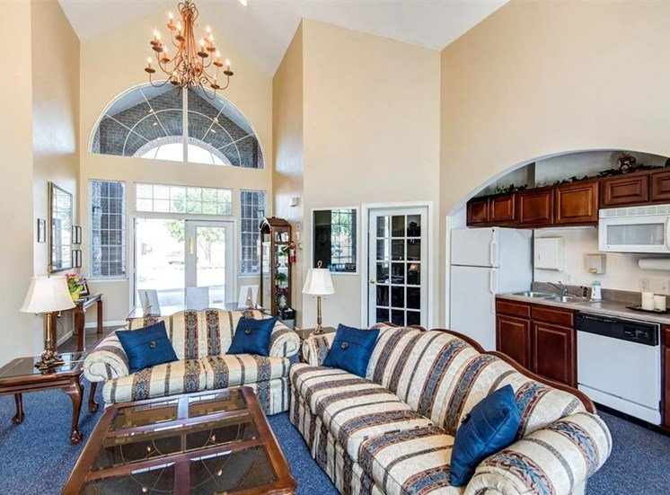 Clubhouse Seating Area with Large Windows Striped Couches with Throw Pillows Next to Coffee Table and End Table with Clubhouse Kitchen in The Background with Wood Cabinets and White Appliances