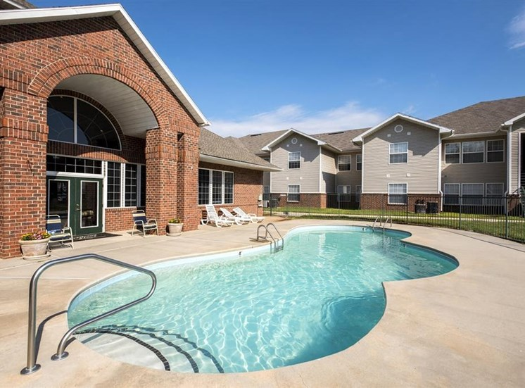 Leasing Office Exterior with Swimming Pool and Sun Deck with Lounge Chairs and Building Exteriors Behind Fence