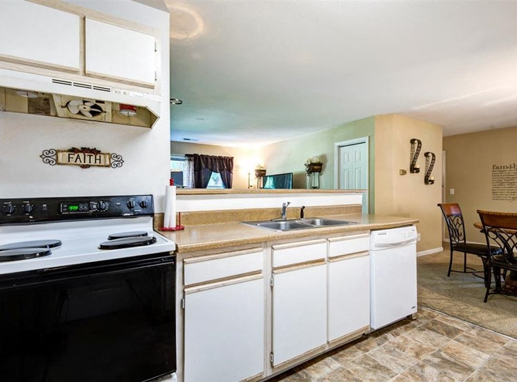 Model Kitchen with White Cabinets and Appliances Beige Counters with Dining Room Table Visible in the Background