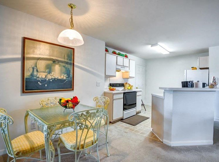 Model Dining Room with Table and Chairs and Kitchen with White Cabinets Counters and Appliances