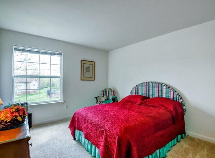 Model Bedroom with a Large Window and Colorful Bed Wood Dresser