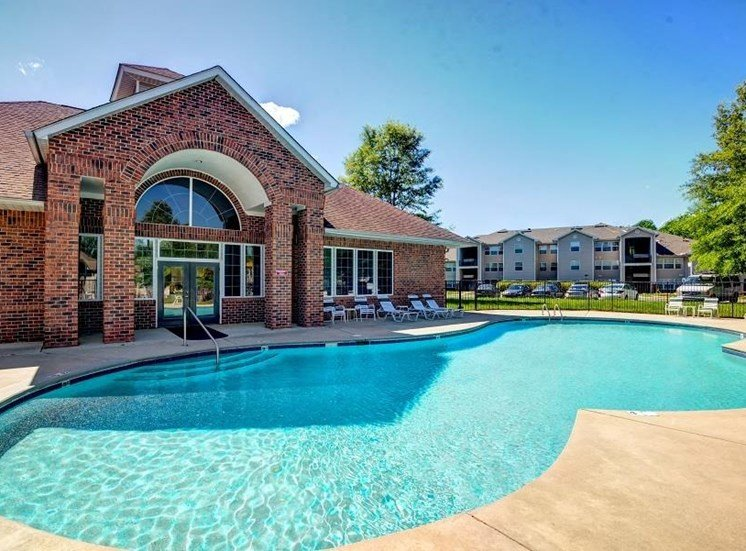 Leasing Office with Swimming Pool with Large Tree and Building Exterior in the Background