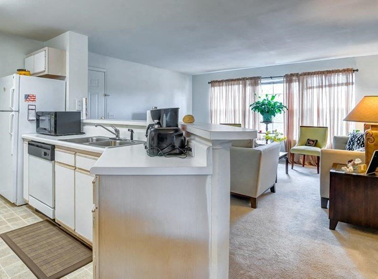 Model Living Room with Furniture and Kitchen with White Counters and Appliances and a Pass Through Breakfast Bar