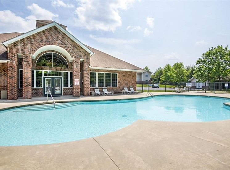 Leasing Office Exterior with Swimming Pool and Sun Deck with Lounge Chairs Near Treeline