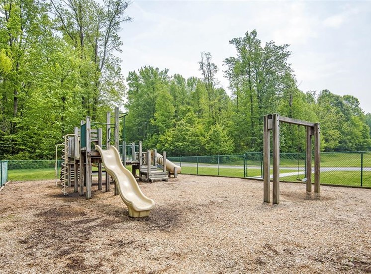 Wooden Playground with Yellow and Green Accents with Swing Set on Mulch with Fence