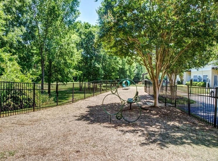 Fenced in Dog Park with Mulch and Agility Equipment  and Trees in the Background