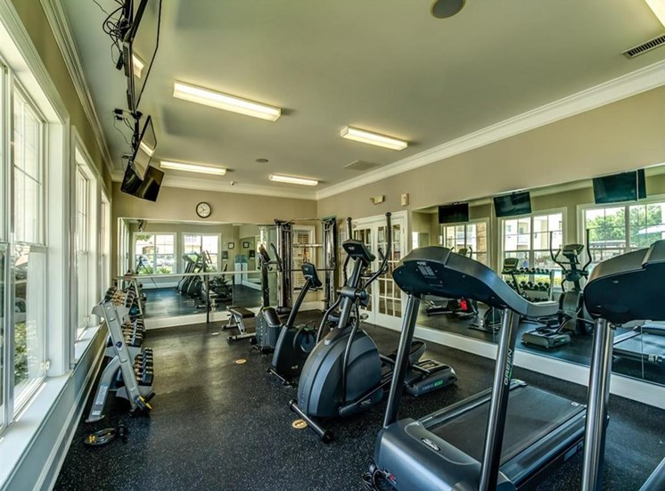 Fitness Center with Cardio Equipment Mounted TVs and Mirror Accent Walls