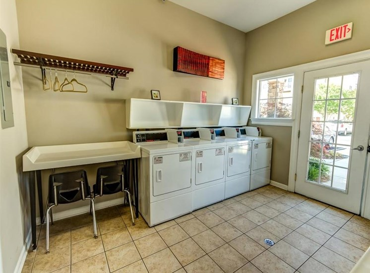 Laundry Center with Machines Next to Folding Counter with Chairs