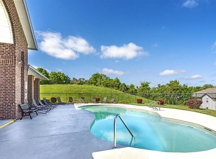 Hillside Fenced in Swimming Pool with Lounge Chairs Near Leasing Office and Shrubs near the Fence