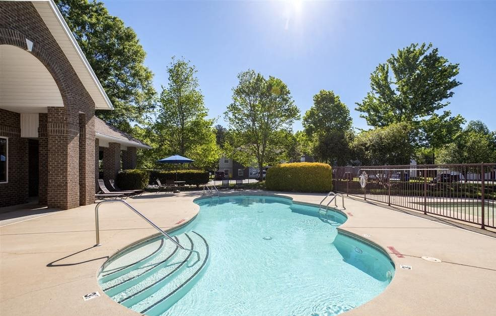 Leasing Office Exterior with Fenced Swimming Pool and Sun Deck with Lounge Chairs Near Treeline