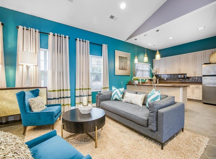 Clubhouse Seating  Area with Blue Armchairs Coffee Table Grey Couch and Blue Accent Wall with Kitchen in the Background