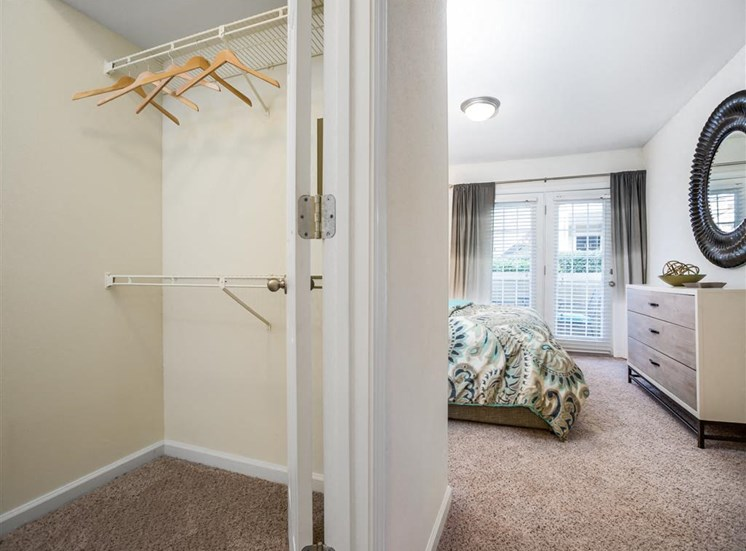Walk in Closet in Model Bedroom with Bed and Dresser