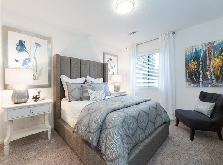 Fully Furnished Model Bedroom with Bed Nightstand and Chair