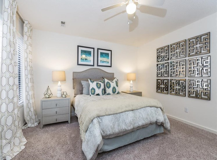 Fully Furnished Model Bedroom with Bed Nightstand and Art on the Wall