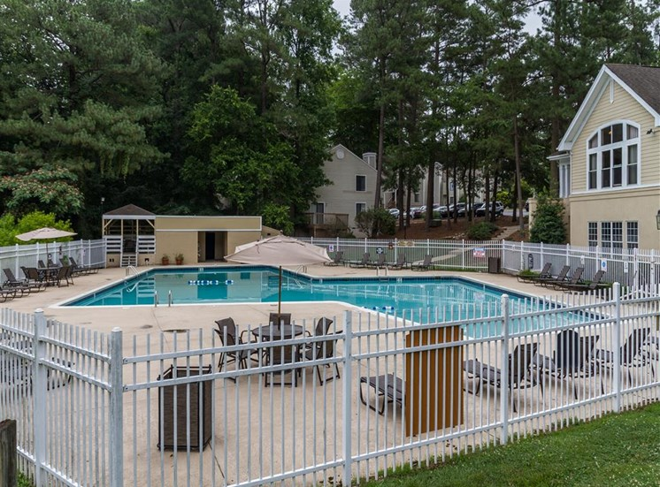 Fenced in Swimming Pool and Sun Deck with Lounge Chairs and Building Exteriors in the Background