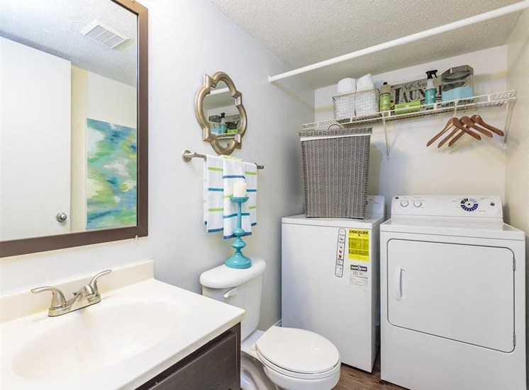 Model Bathroom with Washer and Dryer Below Wire Shelf with Decorations and Supplies