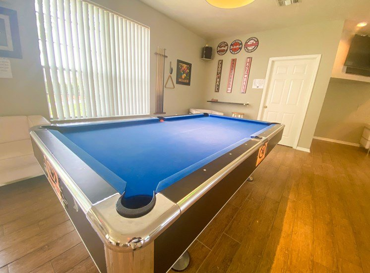 Blue pool table inside the leasing office on wood style flooring with tv mounted in the background