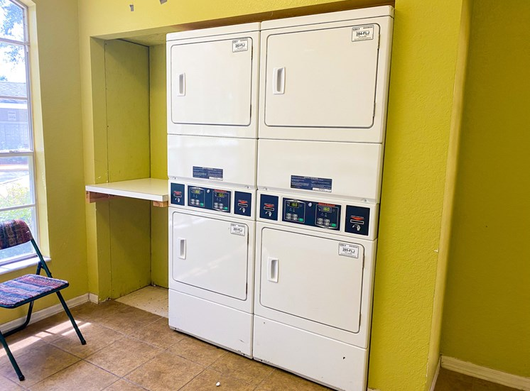 Four Stackable dryers in laundry facility with green walls