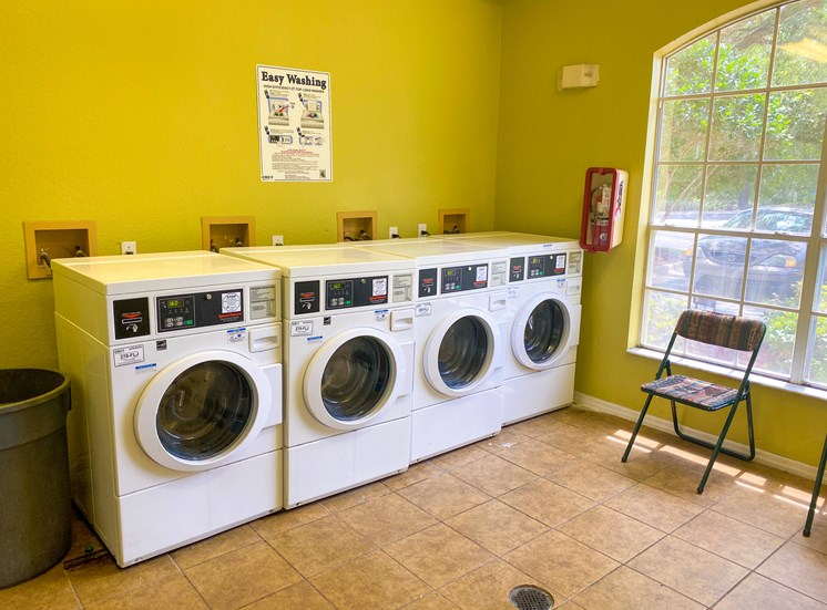 Laundry center with four side by side washing machines.