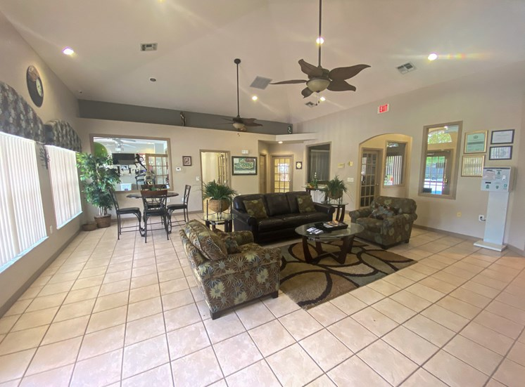 Interior of the clubhouse with ceramic tile flooring, couches, coffee table, and ceiling fans.
