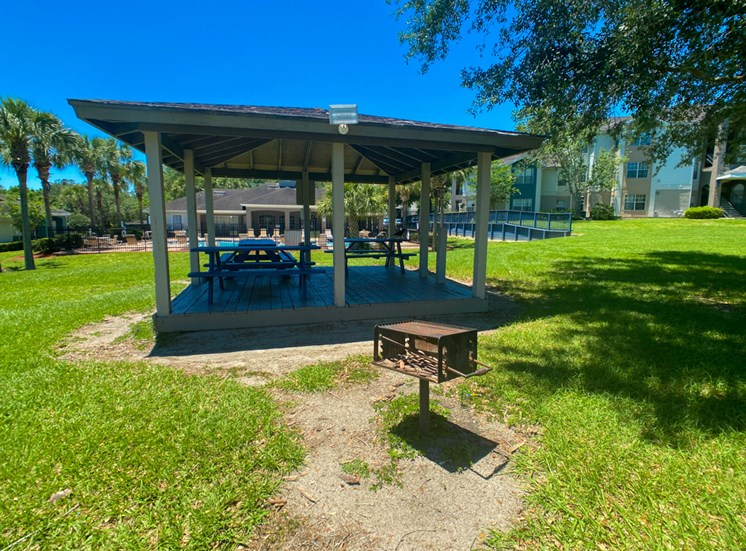 Outdoor covered picnic area with charcoal grilling station surrounded by native landscaping