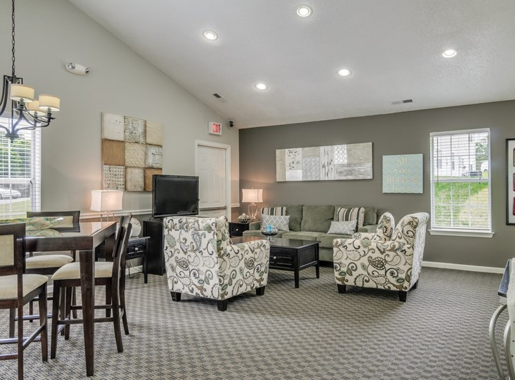 Clubhouse with sofa, coffee table, arm chairs. High top table with chairs. Television on an entertainment center.