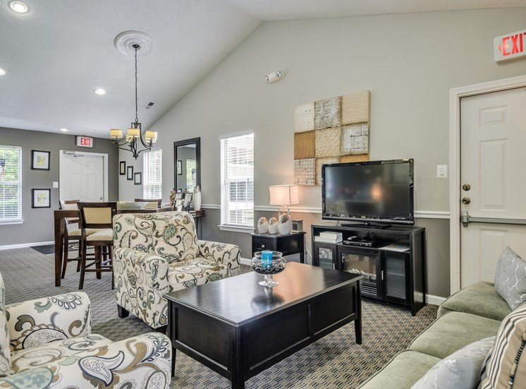 Clubhouse with arm chairs and coffee table. High top table with chairs. Television on an entertainment center.
