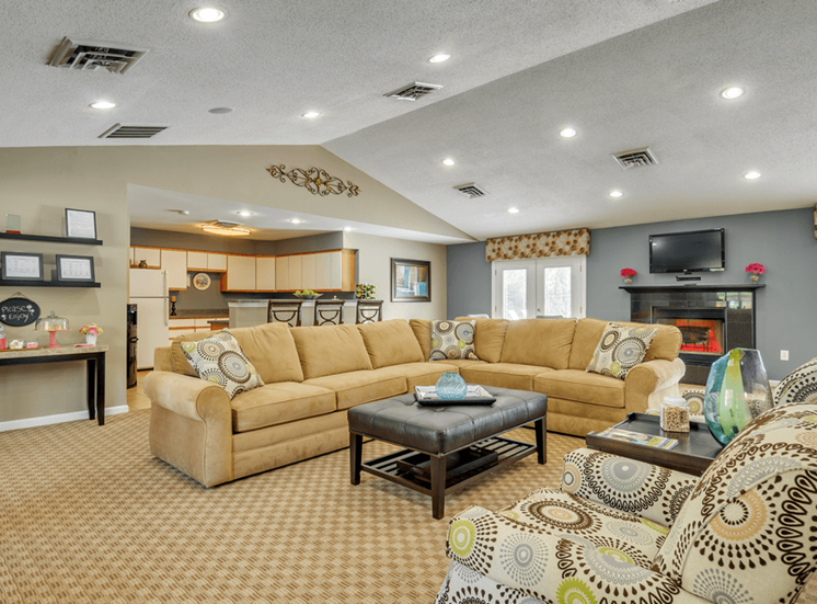 Clubhouse lounge with carpet flooring, couch, chairs, coffee table, fire place, wall mounted television, and kitchen with breakfast bar