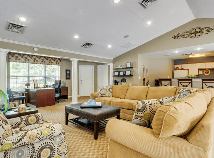 Clubhouse lounge with couch, chairs, coffee table, large windows for natural lighting, and kitchen with breakfast bar