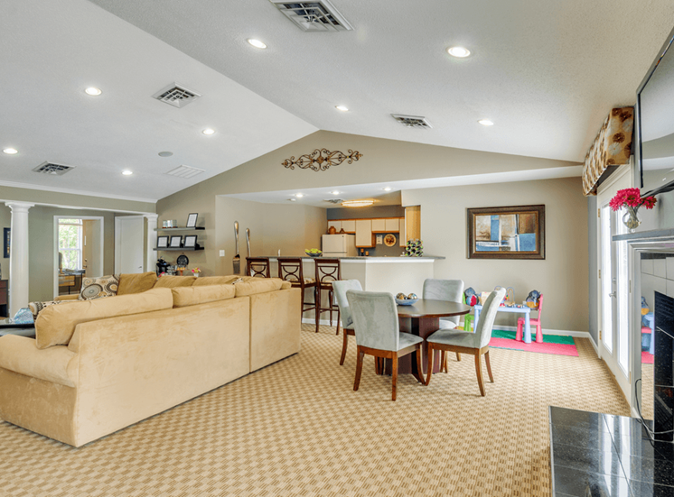 Clubhouse lounge with couch, cafe style table seating, fire place, wall mounted television, and kitchen with breakfast bar seating