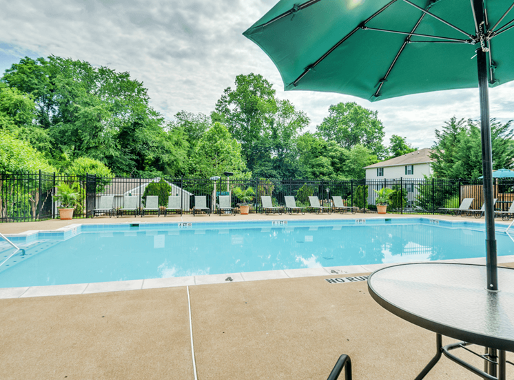 Swimming pool with lounge seating, shaded picnic seating, surrounded by native landscaping, and apartment building exterior in the background