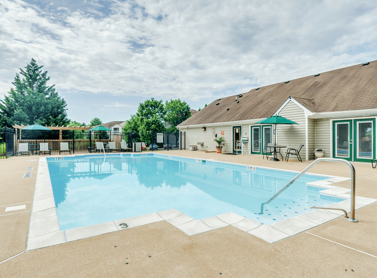Swimming pool with lounge seating, shaded picnic seating, and clubhouse in the background
