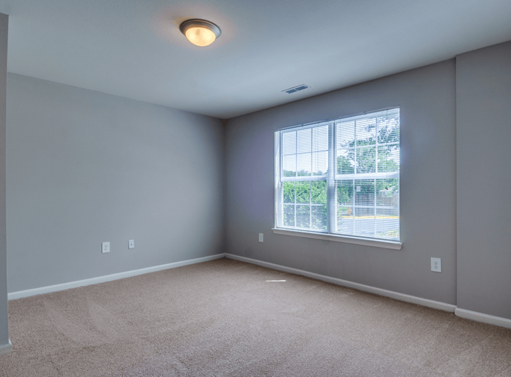 Spacious bedroom with carpet flooring, and large window for natural lighting