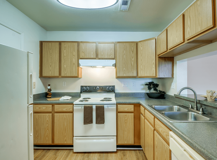 Kitchen with white appliances, hardwood style flooring, and double basin sink