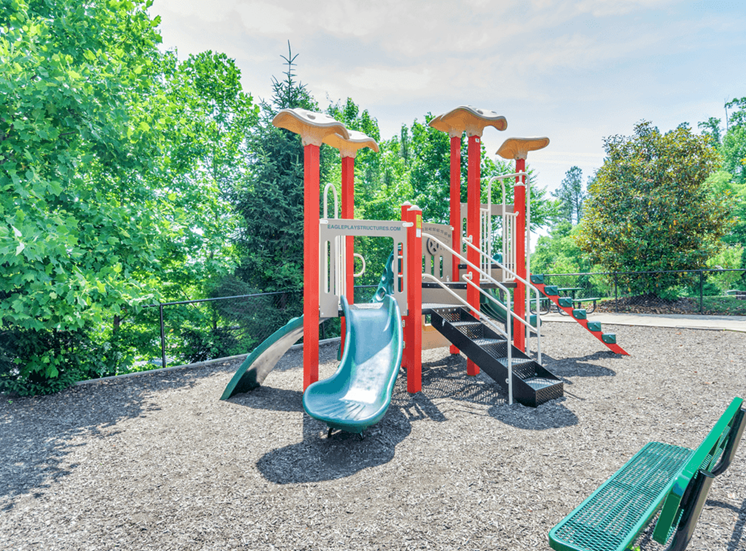 Outdoor playground equipped with slides, latter's, surrounded by native landscaping and bench