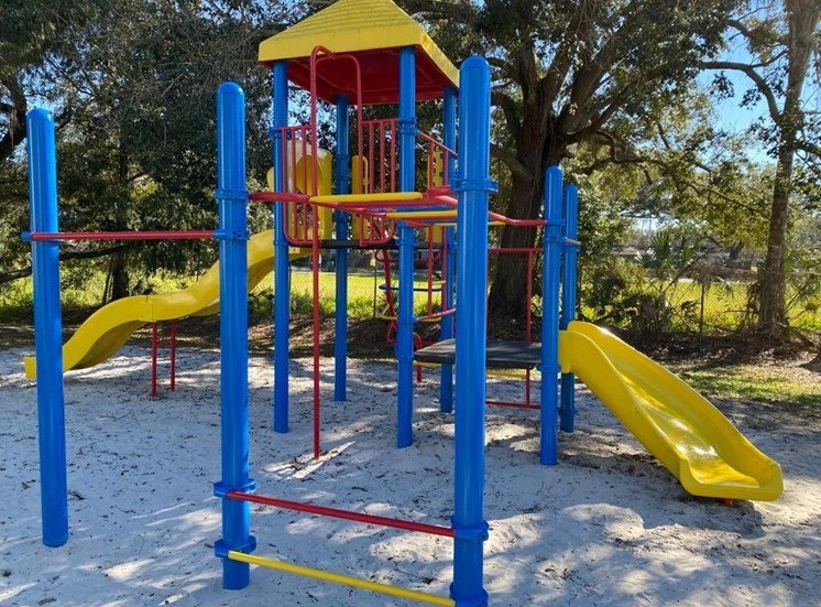 Multi Colored Playground on Sand Shaded by Trees