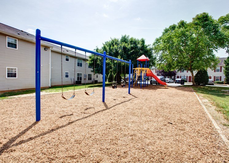 The community playground is surrounded by mulch, grass, trees and apartment buildings. It has 4 swings, and a jungle gym area with a red slide, yellow monkey bars, and stairs.