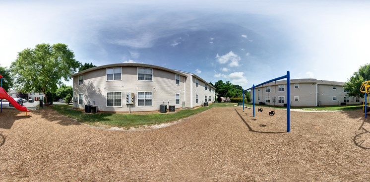 Panoramic shot of apartment building exterior with the playground in the foreground