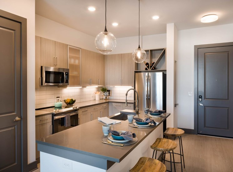 Model Kitchen with Light Wood Grain Cabinets Grey Counters KItchen Island and Stainless Steel Appliances