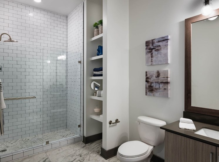 Model Bedroom with Walk in Shower and Subway Tile Next to Built in Shelves