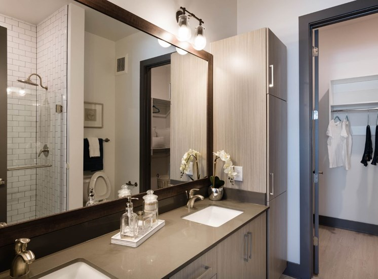 Model Bathroom with Light Wood Grain  Cabinets Grey Counters Wood Framed Mirror with Walk in Shower in Reflection