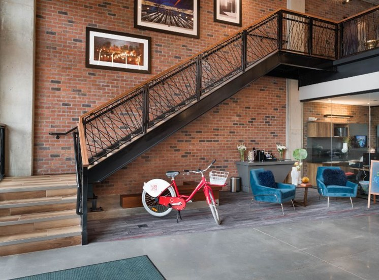 Staircase in Leasing Office Above Red Bicycle Next to Blue Armchairs