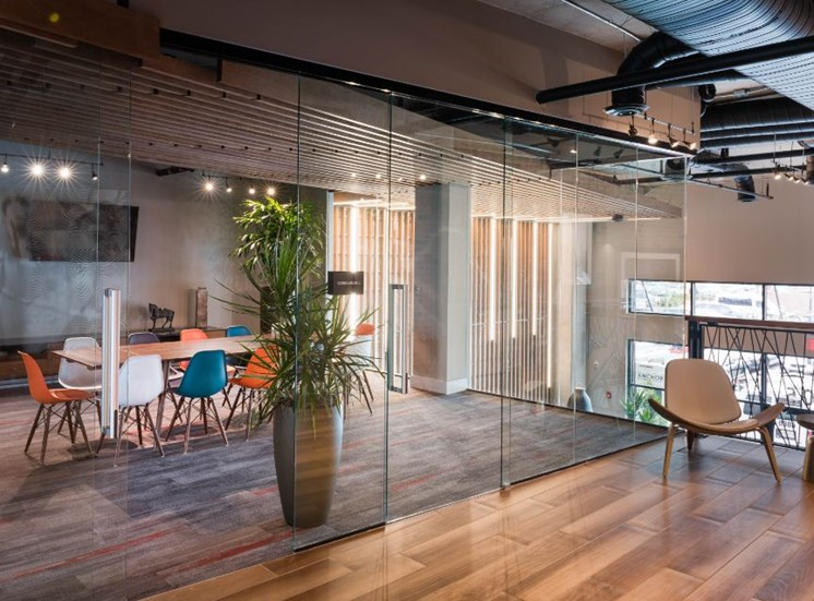 Glass Wall with Open Glass Door To Conference Room with Table with Colorful Chairs