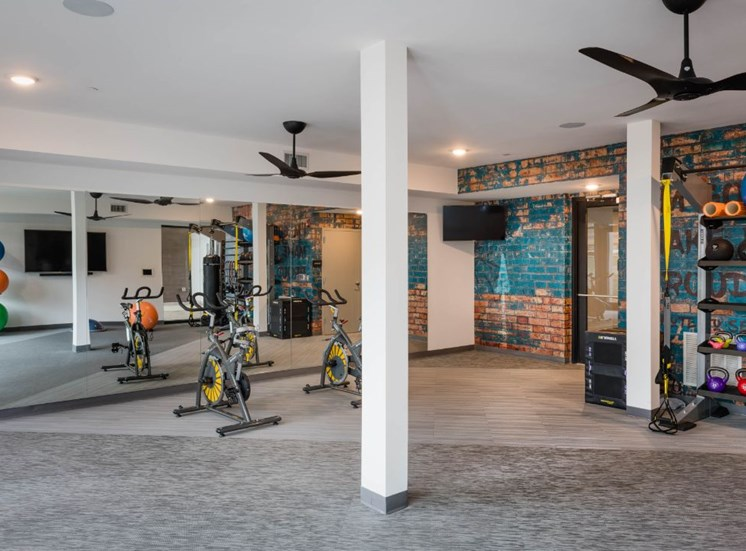 Open Fitness Center with Mirror Accent Wall and Exercise Equipment