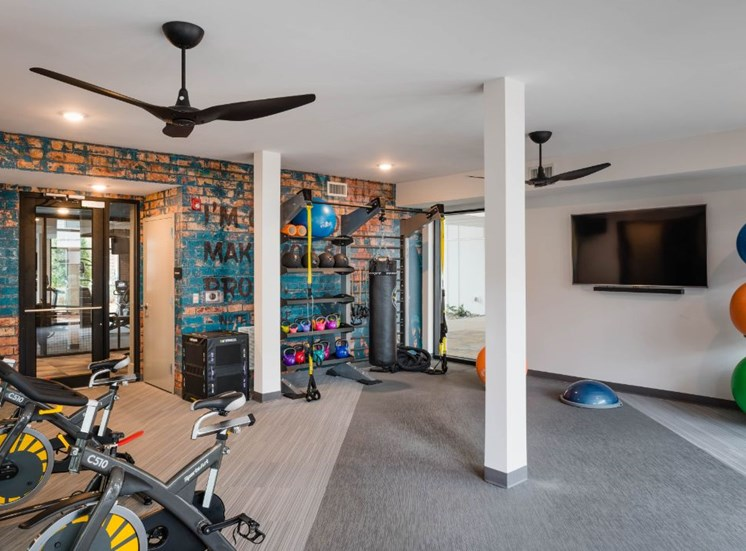 Open Fitness Center with Exercise Equipment and Brick Accent Wall