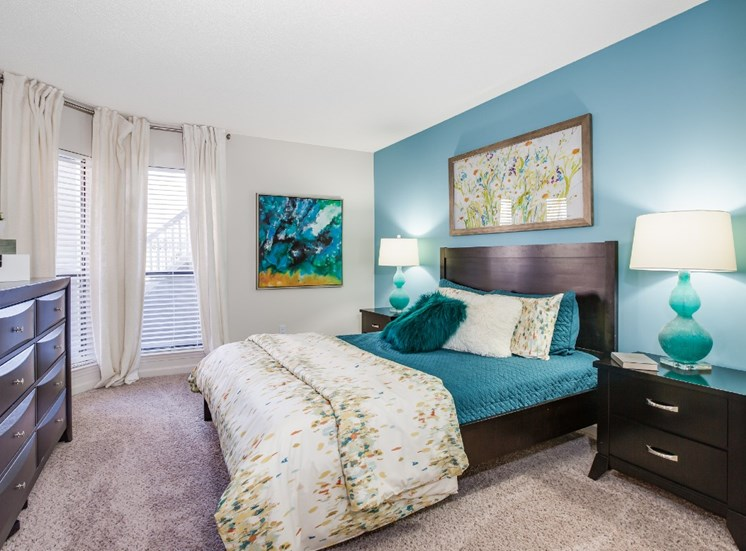 Model Bedroom with Blue Accent Wall Bed Nightstands and Dresser