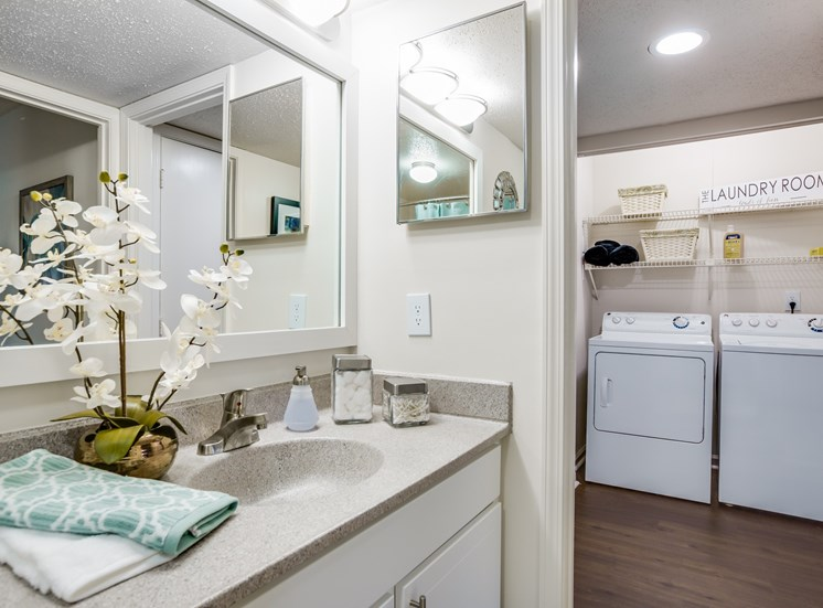 Model Bathroom with Grey Counters White Cabinets and Decorations
